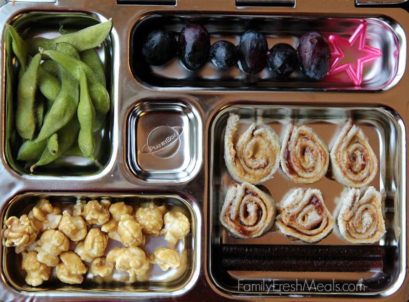 Planetbox lunch packed with grapes, edamame, caramel corn, almond butter and jelly sushi and fruit leather.