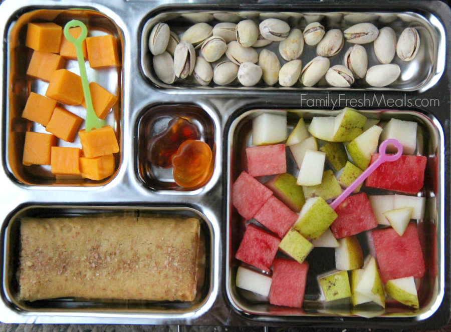 PlanetBox packed with pistachios, cheese cubes, fresh watermelon and pears, breakfast bar and a couple gummy treats.