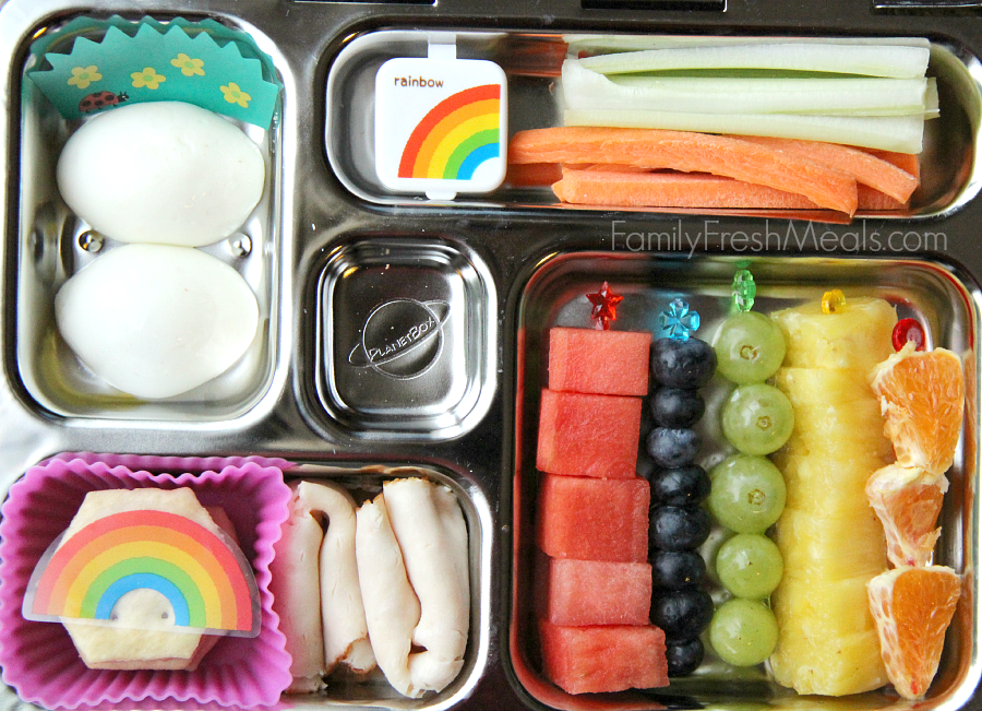 Planetbox lunch packed with celery, carrots and a small container of dip, hard boiled eggs, some lunch meat and crackers and fresh fruit.