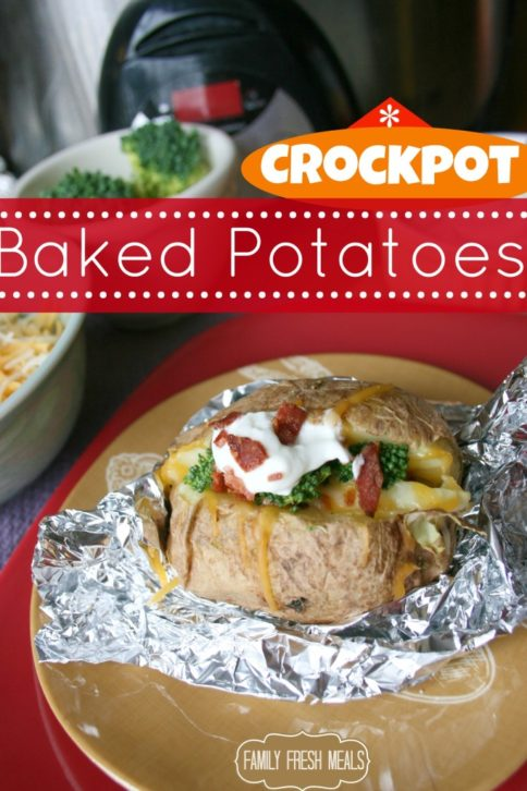 Crockpot Baked Potatoes, toped with bacon, broccoli and sour cream, set on tin foil, on a brown plate