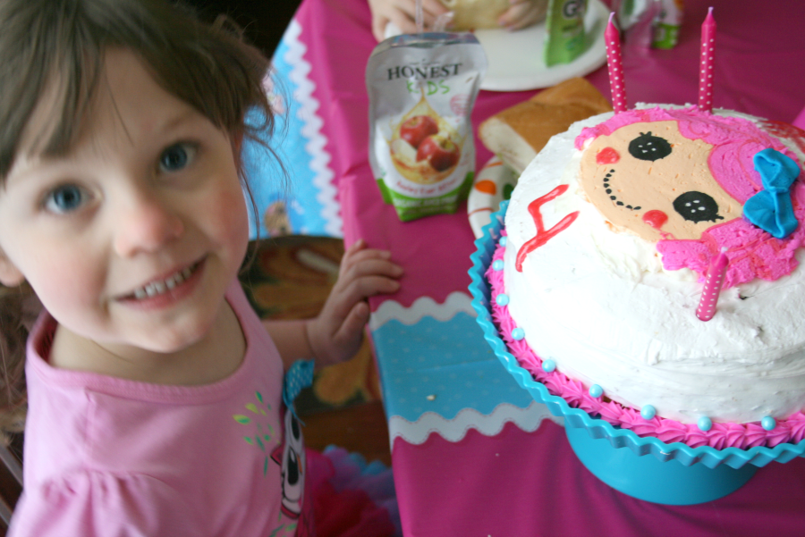 Child sitting at a table with a Lalaloopsy Cake