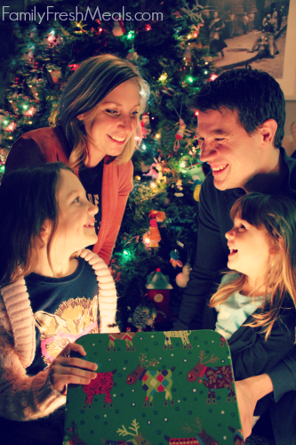 Family gathered around a present smiling