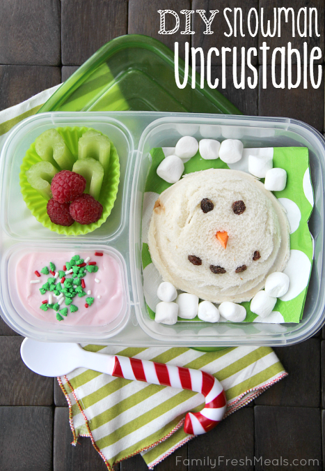 Uncrustable sandwich with carrot nose and raisin eyes/mouth,  mini marshmallow, a celery/raspberry wreath, and some Greek yogurt topped with food sprinkles. All packed in a lunchbox