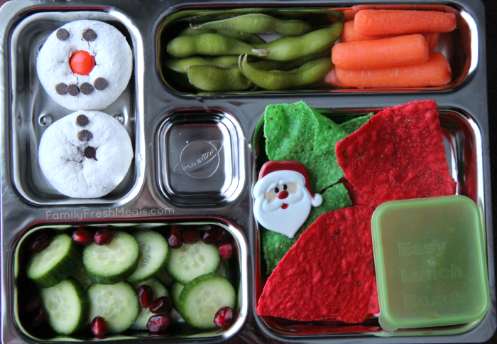 Lunchbox packed with steamed edamame, carrots, tortilla chips and salsa, cucumbers with pomegranate seeds and a mini donut snowman for dessert.