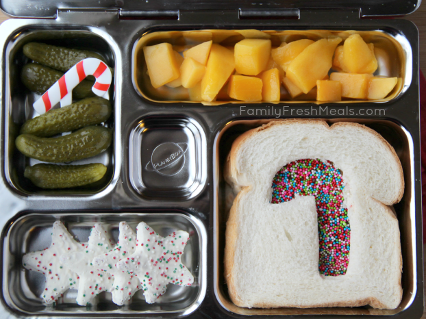 top down image of lunch box packed with mango, dill pickles, a fairy bread sandwich, and a couple star shaped cookies for dessert.