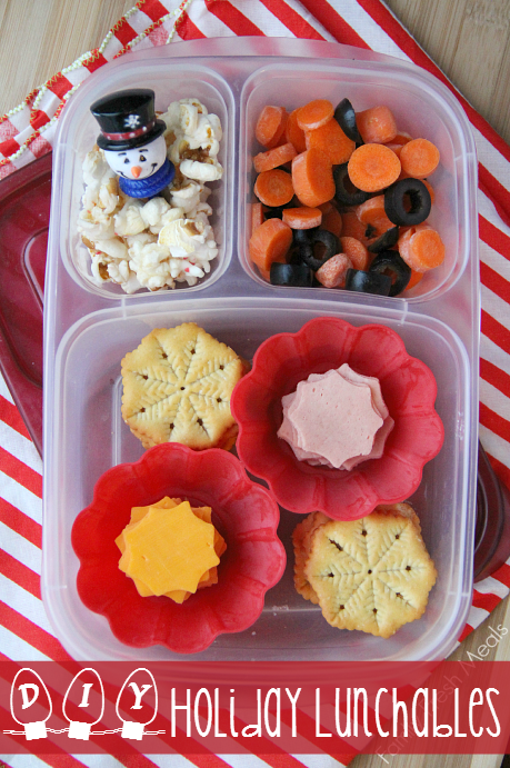 Lunchbox packed with snowflake crackers, deli meat and cheese cut with a snowflake cookie cutter.  In the smaller compartments are some carrot coins, olives and popcorn.