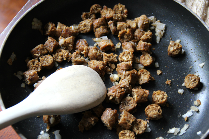 sausage pieces cooking in a pan with diced onion