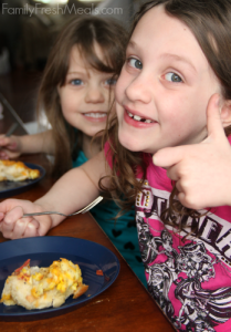 two children sitting at a table eating breakfast casserole