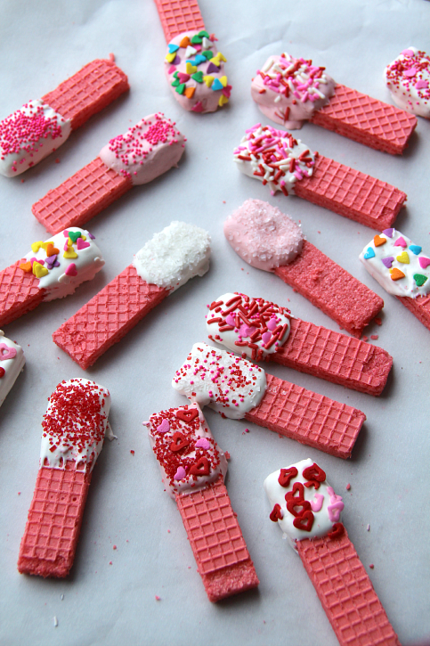 Valentine's Day wafer cookies laid out on parchment paper