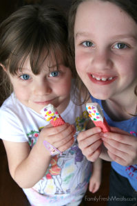 Two children holding wafer cookies