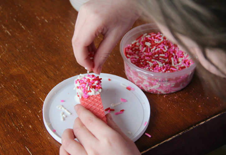 adding sprinkles to the top of a wafer cookie