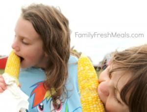 2 kids eating corn on the cob