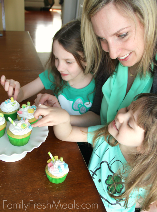Woman and two children sitting in front of some Shamrock Shake Cupcakes