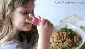 Child eating Crockpot Thai Peanut Chicken with chop sticks