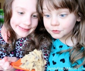 2 children looking at Edible Cookie Dough Recipe with wide eyes