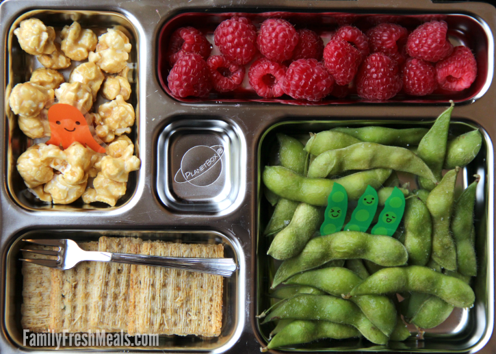 Edamame, crackers and fruit packed in a metal lunch box