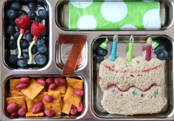 B-day cake shaped sandwich, crackers and yogurt covered raisins, fresh fruit and a fruit leather #7 - packed in a metal lunchbox
