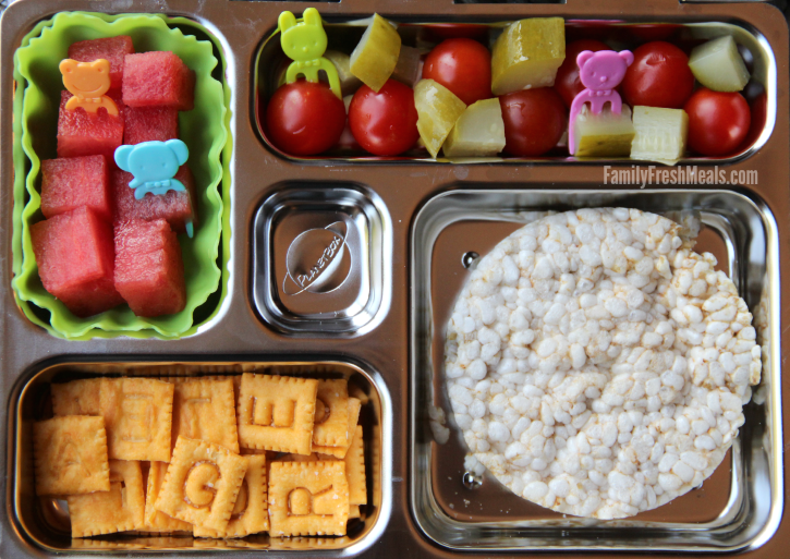 Rice cakes, , fresh fruit and veggies packed in a metal lunchbox