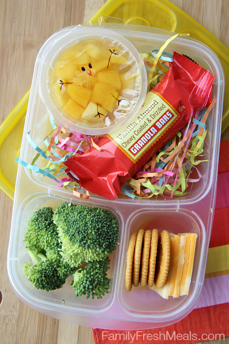 Fun Spring Fruit Cup Snack packed in a plastic lunch box with cheese, crackers, broccoli and granola bar