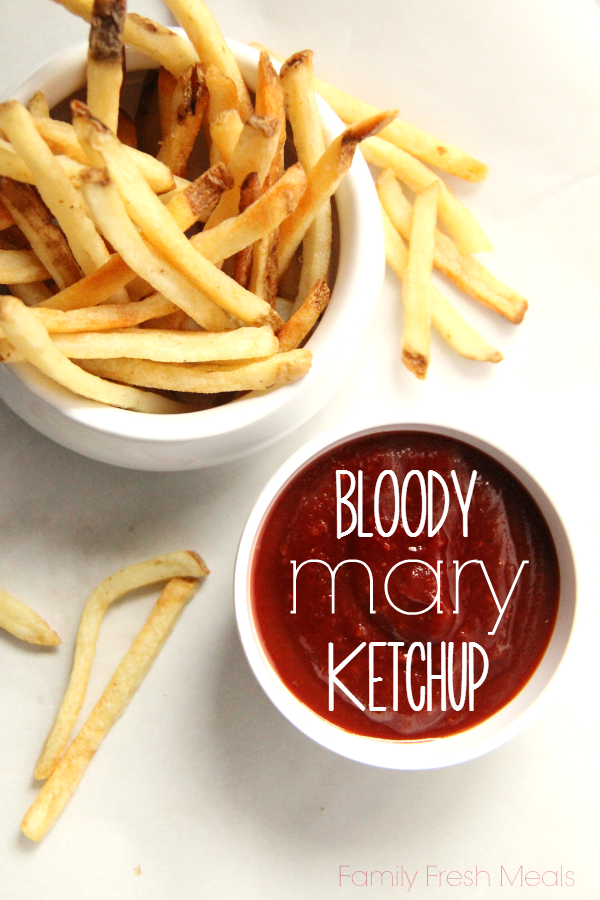 ketchup in a small bowl with with a bowl of fries