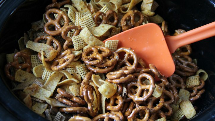 spatula mixing chex mix in a slow cooker