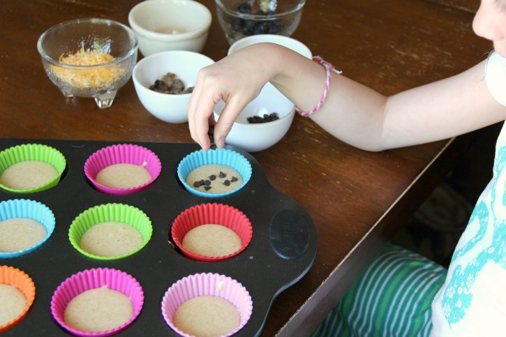 Child adding pancake mix- in ingredients to pancake muffins
