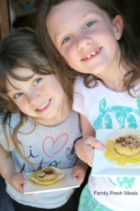 2 children holding plates with Baked Pancake Muffins on it