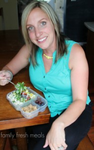 woman sitting with a salad in a lunchbox