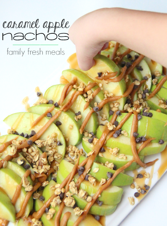 Caramel Apple Nachos on a white plate, with a hand picking up a slice