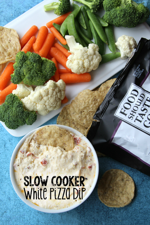 Slow Cooker Cheesy White Pizza Dip in a small white bowl with vegetables and chips