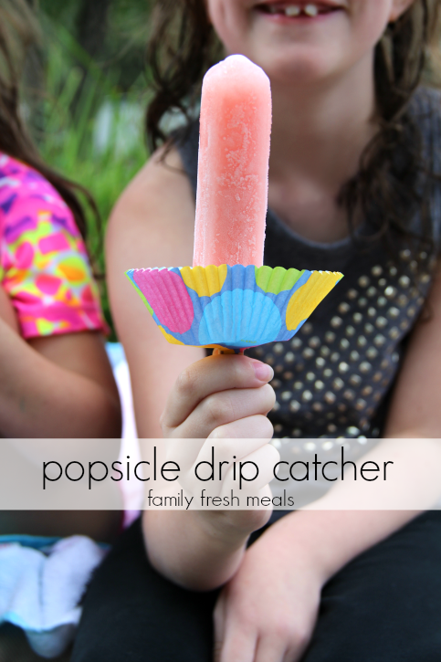Child holding a popsicle with a cupcake liner on the stick