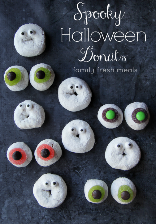 powdered donuts on a table with candy eyes on them