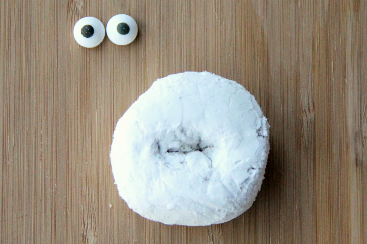 2 candy eyes next to a powdered donut