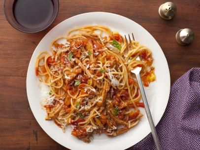 Turkey Bolognese mixed in with noodles on a plate with a fork