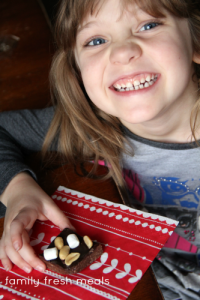 Child smiling while holding a piece of Easy Rocky Road Fudge Bites