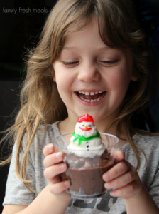 Child smiling while holding a Snowman Cup