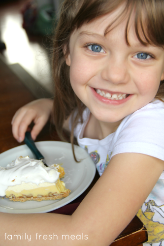 Child sitting with a piece of Triple Layer Eggnog Pie, smiling