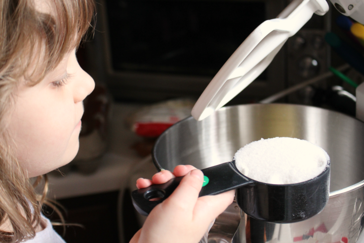 Child holding a measuring cup of flour over mixing bowl