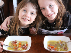 Two girls sitting with bowls of soup