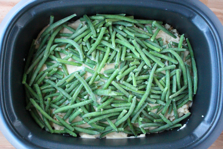 Creamy Crockpot Chicken Stuffing and Green Beans - Frozen green bean placed in black slow cooker