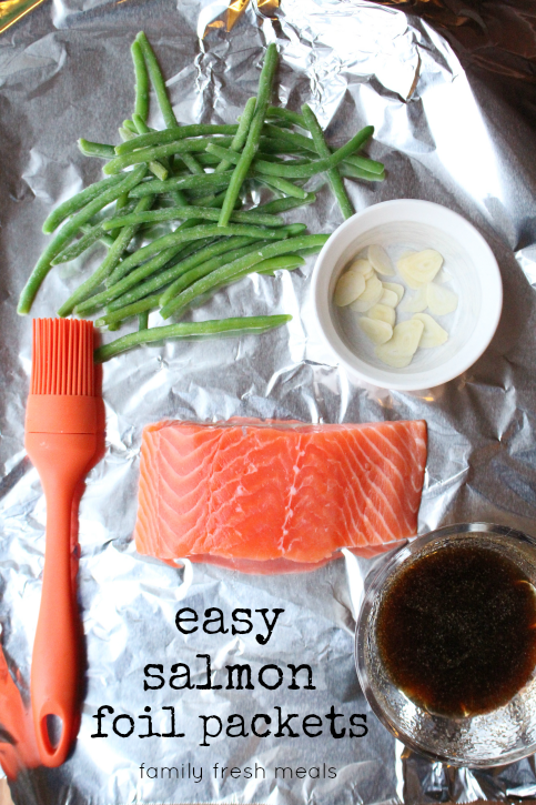 salmon, green beans, garlic slices and a brown sauce in a bowl - sitting on aluminum foil