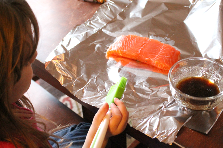 child sitting in front of a piece of salmon that is sitting on foil