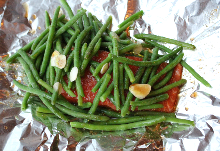 Salmon sitting in the middle of foil, topped with green beans, garlic slices and a brown sauce