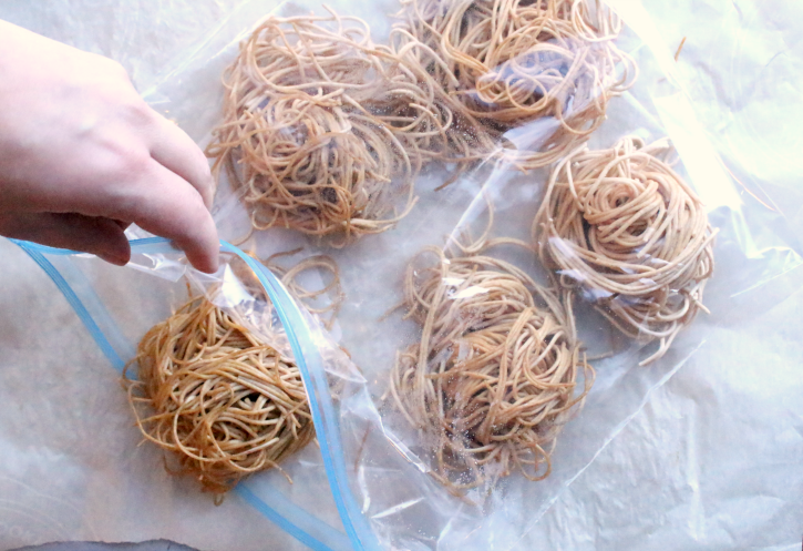 placing frozen piles of pasta into a ziplock bag