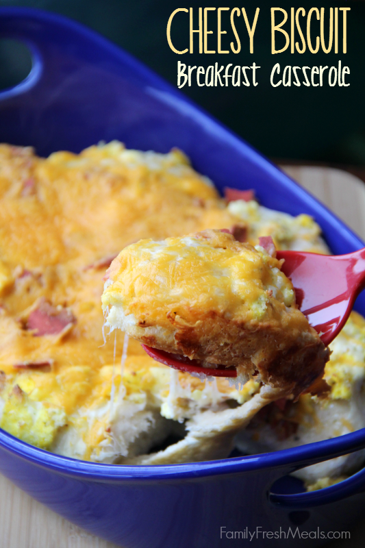 Cheesy Biscuit Breakfast Casserole in a blue baking dish , with a serving spoon scooping some up