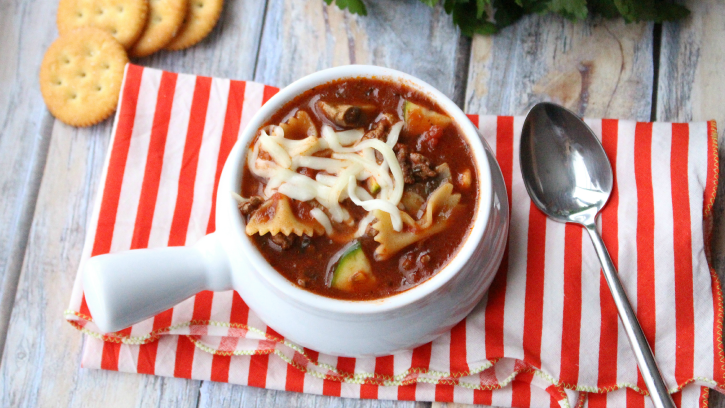 Hearty Slow Cooker Lasagna Soup in a white bowl with a spoon next to it