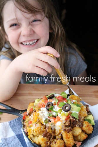 Child sitting with skillet of Tater Tot Nachos
