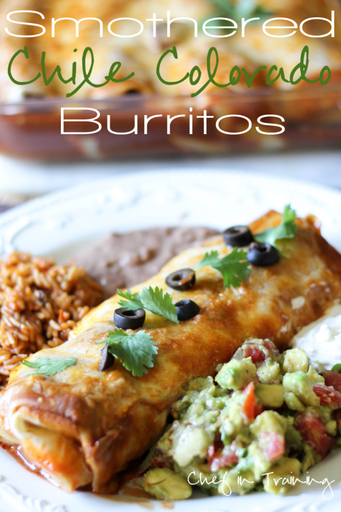 Smothered Chile Colorado Burritos on a plate with rice, beans, guacamole and sour cream