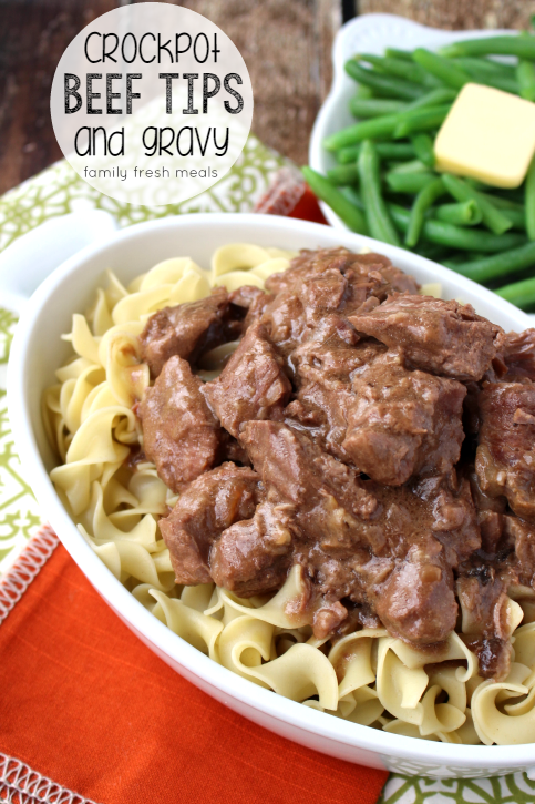 Easy Crockpot Beef Tips and Gravy served over noodles in a serving dish