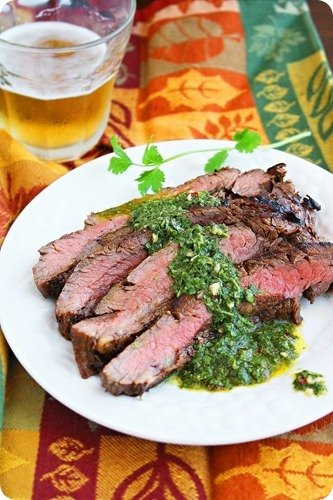Grilled Marinated Flank Steak with Chimichurri Sauce on a white plate
